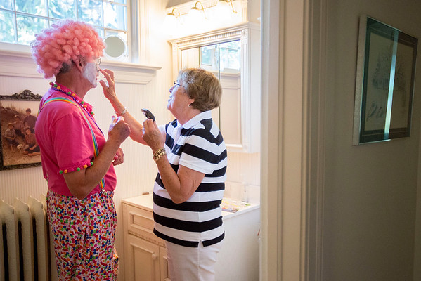 Ralph Cerny, left, holds steady while his wife, Maureen Cerny fixes his clown makeup in their bathroom at their home on July 18, 2016 in Traverse City before Ralph Cerny heads to a gig with the Scottville Clown Band, a group who performs in clown costumes.