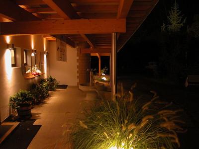 Sanitärbau überdachter Vorplatz Nacht unter Dach mit Beleuchtung; LED-Strahler für runde Sandsteinwand mittlerweile vorhanden.