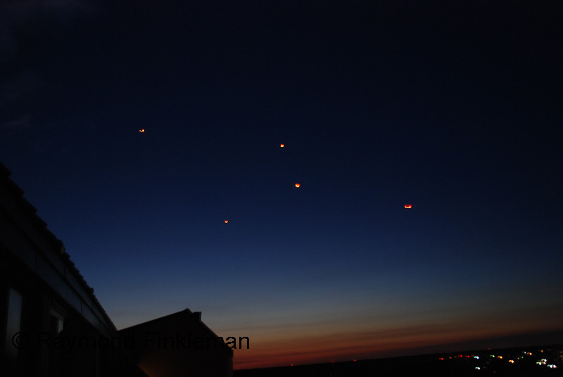 UFOs or probably hot air balloons light by a candle.