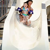 Ashley Swain rides down the slide with her four-year-old sister Johannah at Beulah Park in Alexandria on Thursday. The area set a new record for the month of June at 104 degrees according to the National Weather Service.