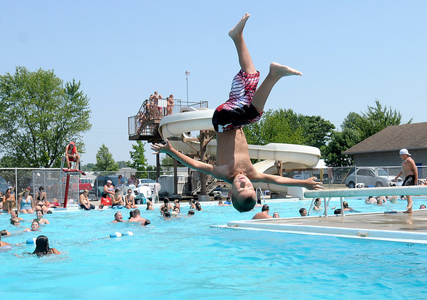 Owen Thompson, 8, flips off the diving board into the pool at Beulah Park in Alexandria on Thursday. The area set a new record for the month of June at 104 degrees according to the National Weather Service.