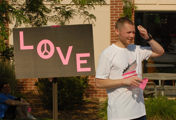 A runner stands by a LOVE sign.