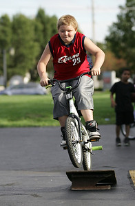 Douglas Wright, age 10, of Elyria, jumps his bike off the home made ramp on Park Place in Elyria Sunday. photo by Ray Riedel