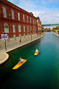 Kayakers paddle through downtown Indianapolis on a canal.