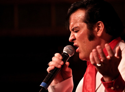 An Elvis Presley impersonator croons aboard the American Queen paddlewheel steamboat on the Mississippi River.