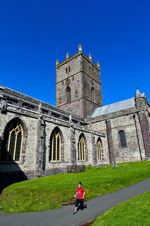 A boy runs along the hulking St. David's Cathedral in St. Davids, one of the larger towns along the Pembrokeshire coast of Wales.