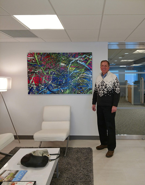 Kevin standing next to one of his images in a commercial install at Keller Williams Real Estate office in Stamford, CT
