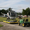 "The helicopters for Mosquito Control are small, light and nimble.  They are kept on pallets and moved around by a John Deer ""tractor"".  The pilot is unhooking the tractor after positioning the helicopter on the pad for take-off."