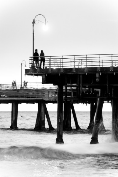 """<span id=""""date"""">_05/18/10_</span> <span id=""""title"""">Couple on Pier</span> It rained a bit today so I headed to the Santa Monica pier around sunset, hoping for something pretty. The sunset was a bust, but I got some good shots anyhow. Deciding on my favorite was a tough call; I chose it because the composition was better than the others. I increased the exposure to give it more of a blown-out look, although it was taken 10 minutes after sunset. I like the motion blur on the 2 couples in the background.  <a href=""""http://www.jawsnap.net/gallery/7157835_BfJPF#540044069_4XnsG"""">[last year]</a>"""