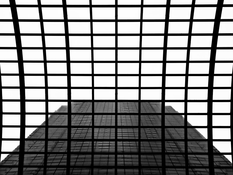 A symmetrical abstract view of the sky and a skyscraper through a glass roof at a shopping center in Tokyo. In pure black and white.