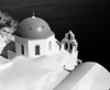 One of the famed blue church domes of Oia on the island of Santorini in the Greek Islands is highlighted against the water in the background. (Scanned from black and white film.)