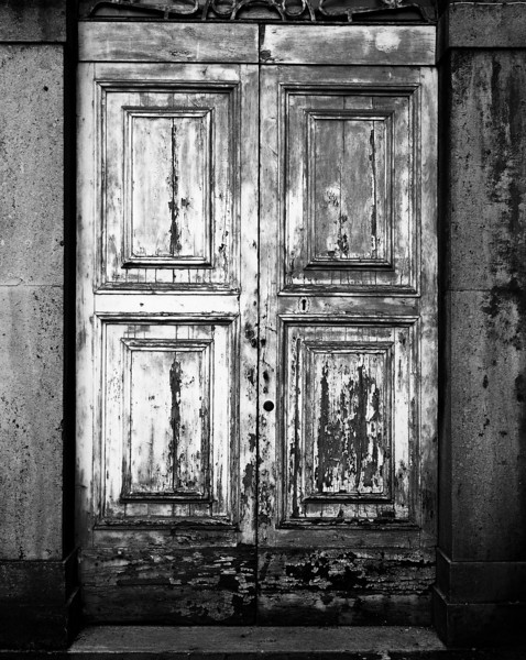 An old, antique wooden door in Orvieto with peeling paint from weathering. (Scanned from black and white film.)