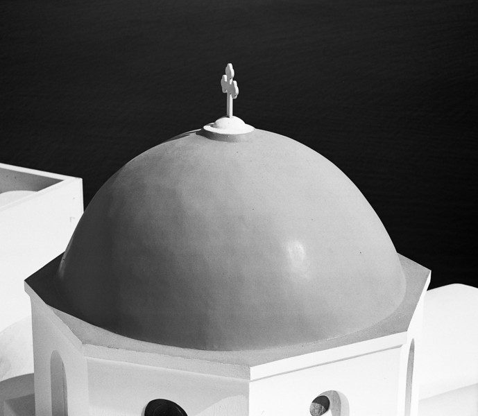 A detailed view of just one of the church domes in Oia and the cross on top outlined against the water in the center of the island. (Scanned from black and white film.)