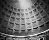 The interior ceiling of the dome of the Pantheon in Rome with a single beam of light from the opening (oculus) at the top providing a source of illumination. (Scanned from black and white film.)