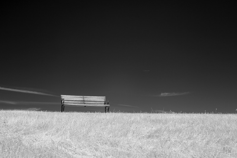 A bench on a field of grass with the sky in the background. Taken with a camera converted to infrared.