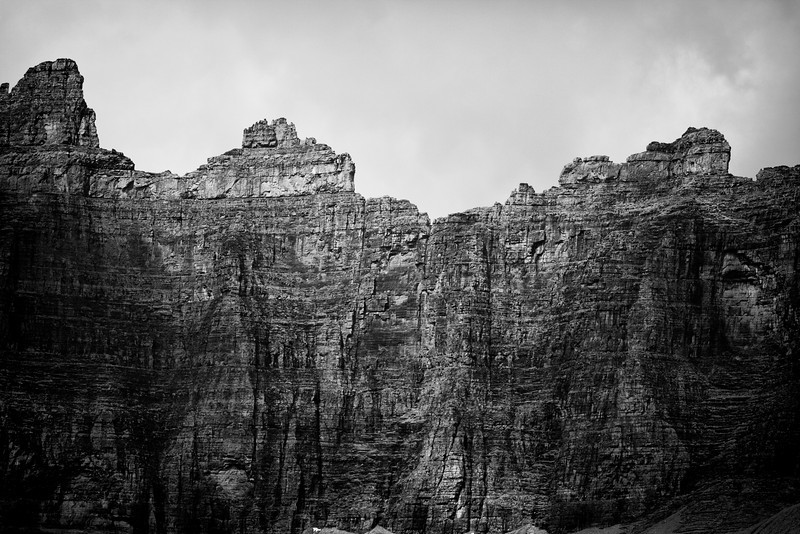 The headwall of the cirque that looms over Iceberg Lake. The cliffs on the mountains form a perfect ampitheater around the lake. Shadows from clouds provide contrast. In black and white.