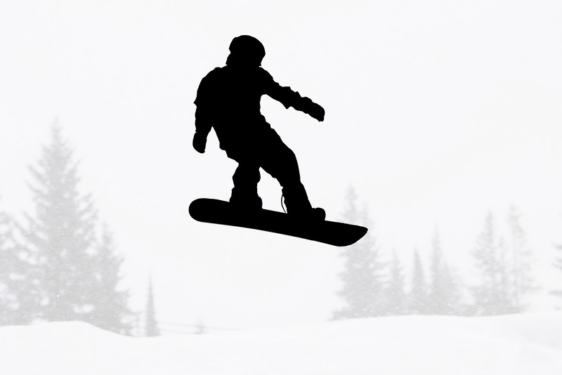 The outline of a sinowboarder jumping in mid-air as he is silhouetted against a landsacpe of gray trees. (In  black and white.)