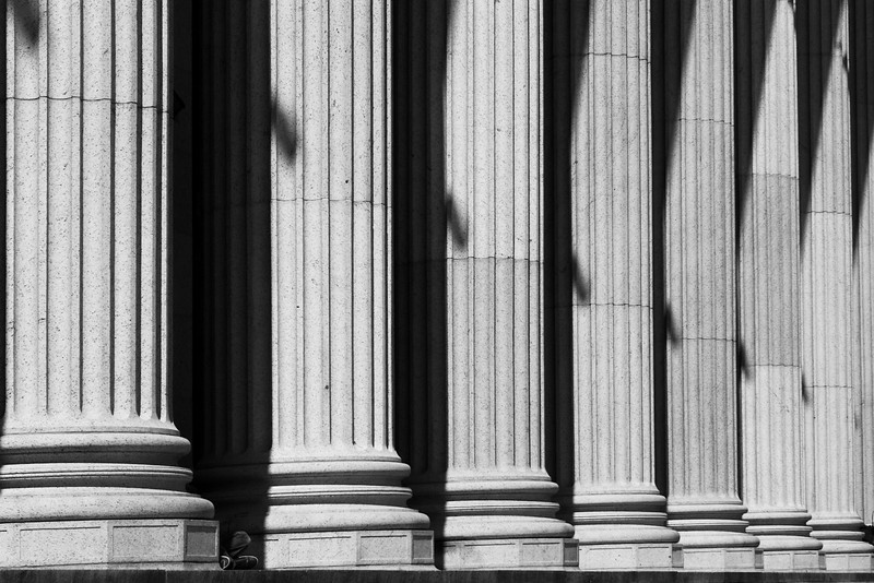 A row of stone columns provide a classical entrance to the New York City post office. In black and white.
