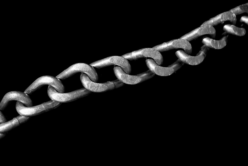 The steel links of a tire chain stretched out diagonally across a tire. Isolated to a black background for contrast.