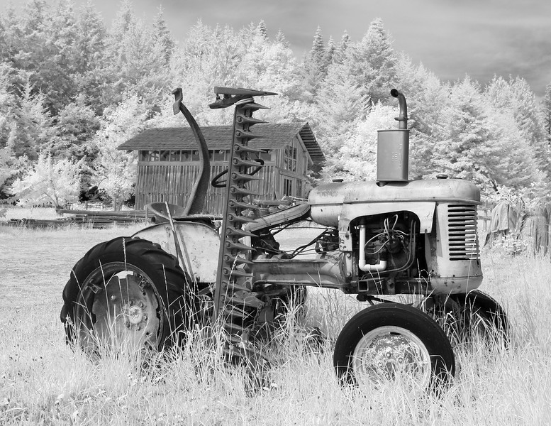 An old tractor on a farm with a barn in the background. In black and white infrared.