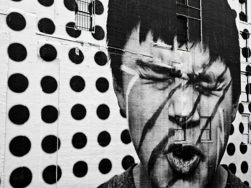 A huge wall mural on the outside of a large warehouse shows an image of a man with face paint wincing in what appears to be pain.