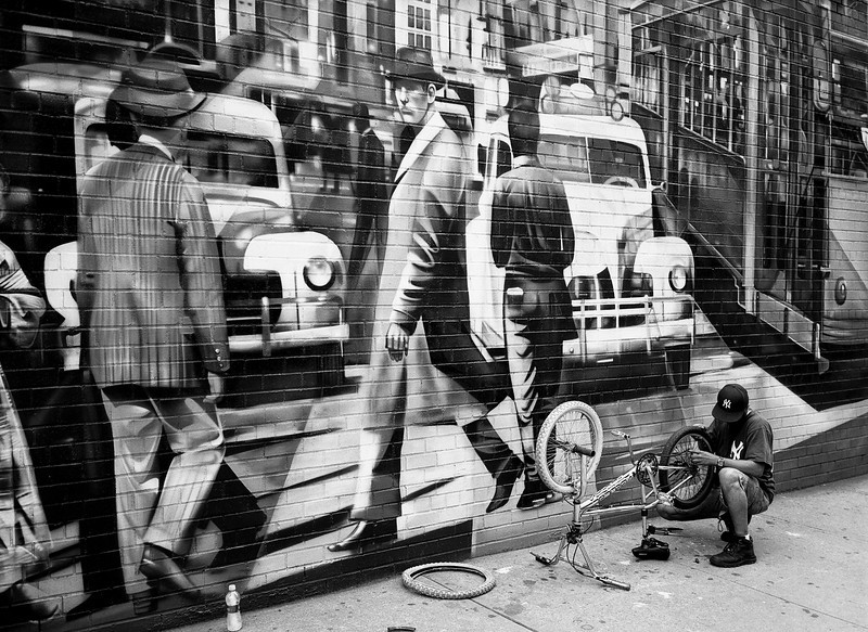 A man repairing a bicycle on a sidewalk in the Chelsea neighborhood of New York City in front of a large scale wall mural showing a different time period. (Scanned from black and white film.)