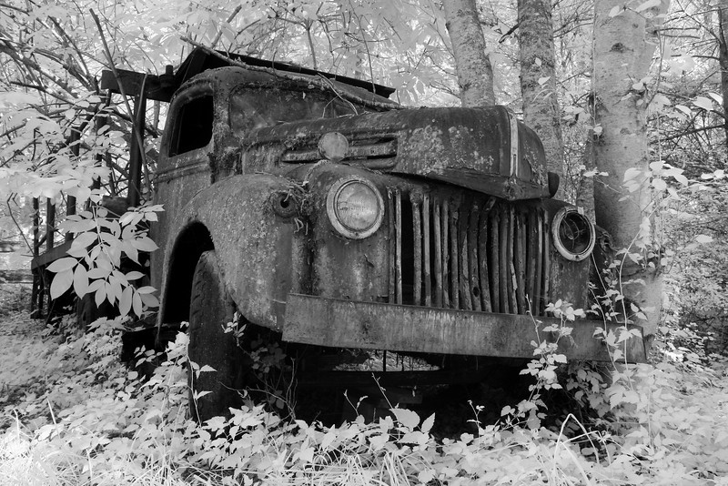 An old, rusted truck that has been abandoned in the country. Taken with a comera converted to infrared light.