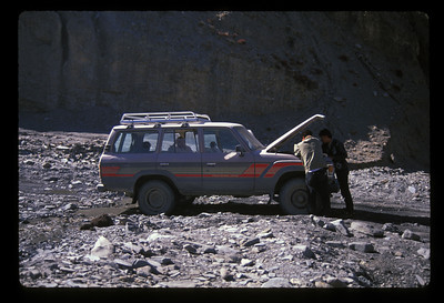 "Eventually, we got accustomed to piling in and out of the LandCruiser. The first time we sat on rocks our hackin' mama shared Lao Lao Tang bubble gum with Mirja and me. Across another mile-wide rock field we did no more than twelve minutes before we sputtered again. <br /> <br /> The first time your car breaks down in the third world is de rigeuer. The second time, if necessary, is included in the package. But now we began to sense a routine.<br /> <br /> Heavy patches of ice hung along either side of the road. At the Dja-So-La pass, even higher than earlier at 5200 meters, we felt much less altitude sickness. The only peak, and it was dominant, stood in snowy splendour. I asked its name.<br /> <br /> Now, way back at the border, when I was happy to get a ride, I got both our ""helper's"" and our driver's names. Since then, I'd lost so much faith in these Han bastards, and talked with them so little, I'd been so unable to kindle a connection that I forgot their names and I didn't care.<br /> <br /> I named our driver ""Noodleboy"" and I just called our little monolingual ""helper,""  ""Sir."" Sir asked Noodleboy what the name of the peak was, they talked, and he turned to me, ""No special name.""<br /> <br /> We sputtered to a stop twice more on the climb down from the pass. Let me tell you that I was frustrated. The LandCruiser idled low but Noodleboy didn't know to shift out of fourth when we'd brake to ease through streams. He wouldn't apply gas, the engine would die, and we'd all hop out and into our routines. <br /> <br /> When we stalled right in the middle of a creek and a bus pulled up, blocked by us, somebody asked, ""How long you been here?""<br /> <br /> I thought I brought down the house by telling them don't worry, they'll fix it in fifteen minutes, they've been doing it all day. The bus sure did think that was a lot funnier than I did.<br /> <br /> *****<br /> <br /> Boys wearing Mao-caps drove past on those one-stroke rototiller-like contraptions. I sat and wondered at the geography - the really awesome upthrust rocks, almost to vertical, caused by the collision of the Indian and Asian tectonic plates. Plus, I wasn't busy. <br /> <br /> Then I'd wonder about us. I marveled at the time, money and effort spent chasing the allure of the vacant, slack-jawed peasant, like, well, our very own Noodleboy. <br /> <br /> And unkindly, I wondered how a driver could be so dense as to not get the even the basics of his job, like the concept of the downshift, or how to press the gas pedal to rev the engine. <br /> <br /> There is one other thing about Noodleboy: except to pass, he drove on the left, even when the left was a precipice, even in fourth gear approaching the crest of a hill. All the time. The whole trip. Every minute. But in Tibet, driving was on the right.<br /> <br /> *****<br /> <br /> Once when we were broken down a LandCruiser with three Europeans and a real English-speaking guide stopped to help. I explained to the Real Guide how Noodleboy would let the engine die and they talked it over but nothing changed. That LandCruiser stayed with us for a while, as if to rescue us if our LandCruiser finally gave up. <br /> <br /> This slowed them down considerably. Finally, at one stop the one Euro-guy slammed the door and theatrically started walking ahead into the desert and I was secretly with Noodleboy when eventually we thundered by him and covered him with dust.<br /> <br /> I asked if I could drive and they just laughed."