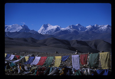 We stood a little tight in the chest, temples pounding, at the prayer flags at the Lalung Leh pass at 5050 meters (16570 feet), and gazed on the peaks of Xixibangma, at 8012 meters, to the west, and Cho Oyu (8153) off to the east in the Qomolangma Nature Preserve. Qomolangma is the local name for Sagarmatha, or Everest, and Cho Oyu is the highest peak in the range west of Sagarmatha. Everest would come.<br /> <br /> We had a little engine trouble, still in sight of the prayer flags. The LandCruiser was idling a little low and they had to climb up under the hood to prime the carburetor. While they did, Mirja and I clambered back out for more of the view, the cold, dry wind chapping our faces, and once the engine fired we moved on. Thrilled at the prospect of Everest ahead, we had no idea how much time would be spent under that hood. <br /> <br /> By midday we were blazing across Tibet. The boys passed between them strings of yak cheese. <br /> <br /> *****<br /> <br /> There were no more bushes - just patches of grass. You might have been watching the blue of the ultra clear sky and the brown earth through a wide angle lens. It all stood in such magnificent contrast, pictures weren't helpful to convey it.