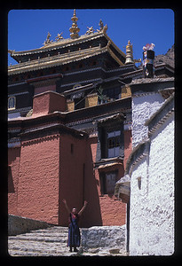 """After a Xigatse walking tour I felt there was nothing clean in Tibet. It's one thing among nomads, or in towns with no electricity (much less plumbing), but here in the second city every sidewalk smelled of piss - every single one - and so did the famous Tashilumpo monastery.  One monk-boy there begged for money - kind of in contravention of monkhood, I thought - and at the free market outside the monastery adult women had this irritating way of insistently laying on your arm begging - the entire length of the market.   The monastery was superlative though, majestic on a hill, a warren of cobbled alleyways and cooled out dogs in the sun. It made your heart pound to climb the steps. I climbed up some maintainence stairs inside the main gate to get a picture of the whole complex and for my trouble a furious monk hurried over to accost me as we walked out.   Mirja noted, """"Now you've pissed off two Tibetans in one day - a monk and a 'helper.'""""  It was a glorious, beautiful spring day, the new, vivid green of young leaves, bright sun that burned your skin in just an hour, maybe the nicest single day I have ever been in - except that the next day was just as nice.  *****  I wasn't giving them any excuse. I watched the sun's first rays strike the prayer flags on the hill behind Tashilumpo monastery from the cool of the front of the Xigatse hotel at 8:00 sharp. By 8:20 I was pretty discouraged and by 8:40 I found a tour bus driver who made me understand he was leaving for Lhasa at 10:00 - but I didn't know how to ask him if he had room for us.   By 8:45 I was in a back office trying to raise Lhasa over the phone when Mirja called down the hall that they were here. Off we went, including, incidentally, our new permanent friend the hackin' chick, who was on a free ride all the way to Lhasa.  As a second city, much as I'd like to, I can't say Xigatse impressed very much. Outside the Panchen Lama's headquarters  there was only the barren, blue-collar feel of a hardscrabble fron"""
