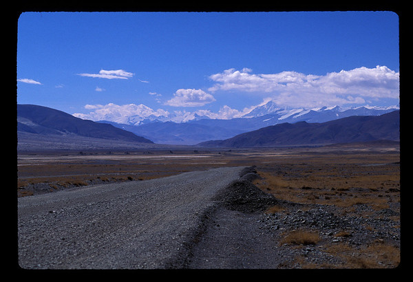 """The pavement ended, as it did after towns. Dry as it was here, still there was a light mist hugging the earth. While we woke with no electricity in the hotel, it still felt closer to civilization than the day amid the nomads.   One of those ubiquitous blue Chinese trucks threw up dust ahead so we couldn't see for several kilometers, as we climbed slowly out of a dry, gray gravel gulch. Peaceful, empty landscape scrolled by for an hour and more,  cooking fires rising from settlements and streams glinting in the slant of the early morning sun.   Another unintelligible mantra, carved in giant characters, stretched across a hillside. Gradually, a few at a time, trees popped up around settlements - but nowhere else - until eventually a thick stand of trees lined the riverbanks at an unnamed village. Ten army transport trucks convoyed by. More yaks. A dust devil out in a field.  A series of long valleys stretched to the horizon, then again, and again. Snow patches dotted the stark brown hills and clouds would form, little cumulus puffs, out of mere air. You could just sit and watch them, and with a long horizon and plenty of time, that's just what we did. A sing-along broke out to the cassettes for a happy couple of hours.  *****  Xigatse is Tibet's second city, former home of the Panchen Lama with his residence, Tashilumpo Monastery - one of the few monasteries allowed by the Chinese to stand (because of a deal with the devil by the previous Panchen Lama - the incarnation of the Panchen Lama who succeeded him - who is just a boy now - was summarily arrested and smuggled to house arrest in Beijing).  The Tashilumpo Monastery and the best hotel in Tibet outside Lhasa both gave Xigatse a certain allure. So when we pulled up to Friendship Hotel #2 instead of our promised and paid for Xigatse hotel - the one with the toilets - the whole tenuous peace broke down.  I insisted we had to go the Xigatse Hotel. Sir, our """"helper,"""" turned around full to talk to us for the first time """