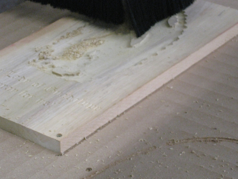 This is a complicated piece to machine, requiring several passes, as various features in the finished product are developed.  The dust and debris from the cutting action is removed by a dust collector as the job proceeds.