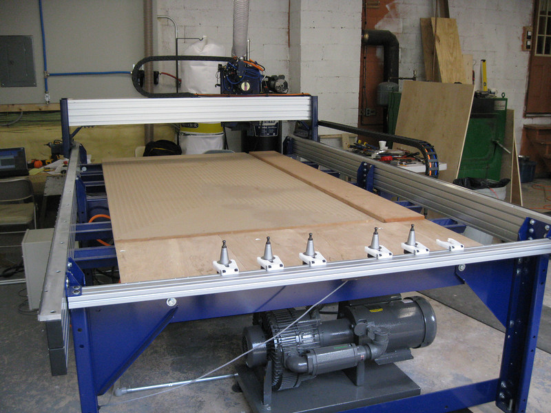 The tool consists of a carriage that allows precisely controlled motion of a cutting head in all directions, including vertical.  The material to be machined is affixed to the table, and may be held there by vacuum suction, provided by the vacuum pump visible below the table working through a permeable board.