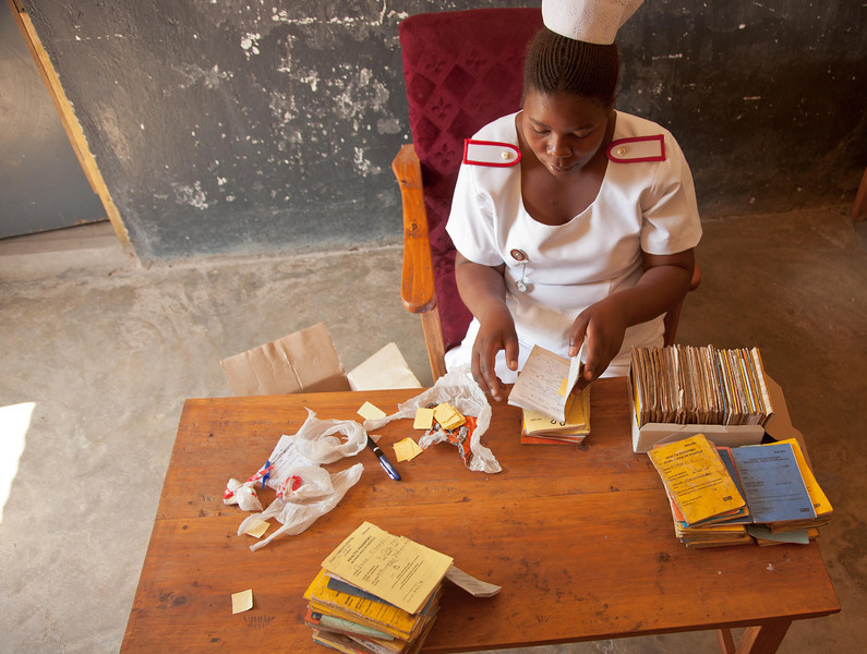 "Rachel Sajeedoo, a health-care nurse in rural Malawi assigns numbers to several hundred ""health passports"" belonging to HIV-positive patients who have come for their monthly medication and counseling."