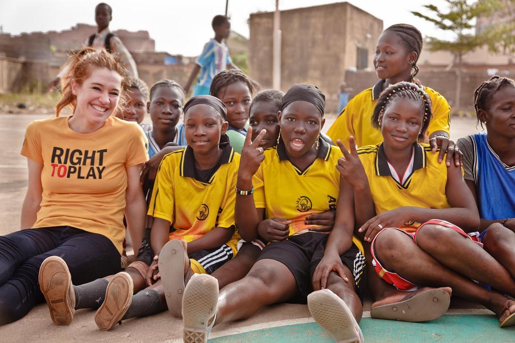 Clara takes a break with  baskeball players at Sebenikoro field, Bamako, Mali