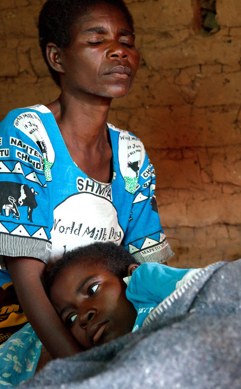 Twelve-year-old Yanjanani, who tested positive for HIV after she was raped by a man behind her school, lies with her mother, too ill to sit.  Her case was dropped by the police who claimed the perpetrator's family had told them that he had settled privately with the victim's family.  Yanjanani's mother vehemently denies this; a local Child Protection Officer familiar with the case suspects the police were bribed.  Regardless, the police has an obligation to enforce the law.  Yanjanani passed away less than one week after this photo was taken. Malawi, 2013