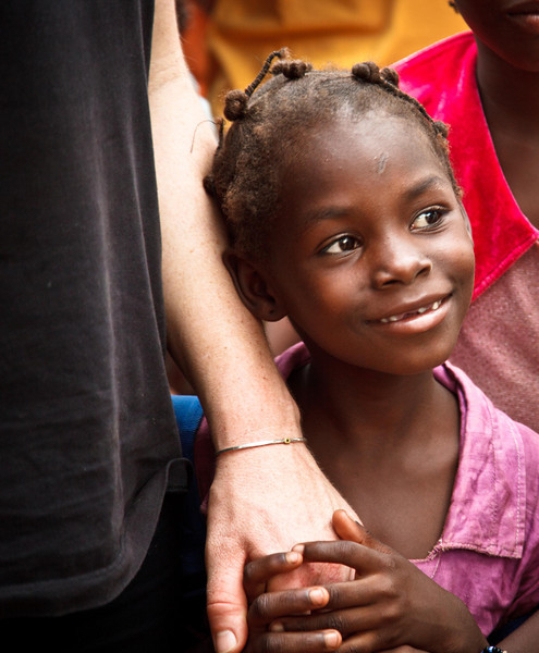 A young girl holds Clara`s hand.
