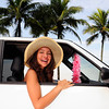 car rental: happy woman in her car near the beach
