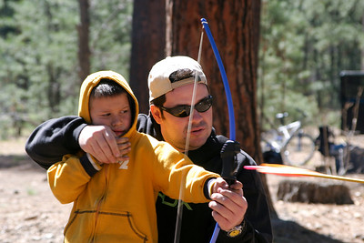 Papa helps Merek shoot an arrow for the first time.