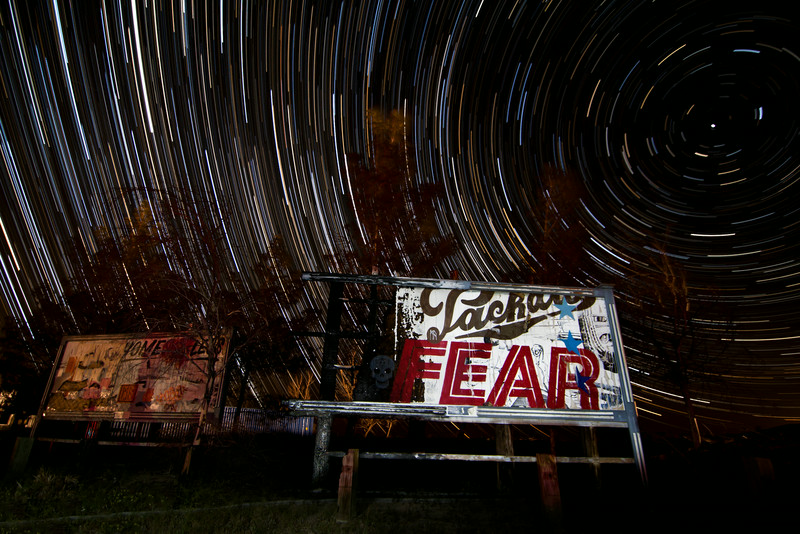 """On our way back from Las Vegas, we stopped off at the abandoned Rock-a-Hoola waterpark to shoot some star trails. Since I've done a few here already I had to find something new to use for the subject. I decided to run my camera infront of some of the """"billboards"""" that TrustoCorp painted."""