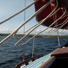 Aboard Winkle Brig 16, reefing lines flying in the breeze with Hopeman Harbour in the distance.