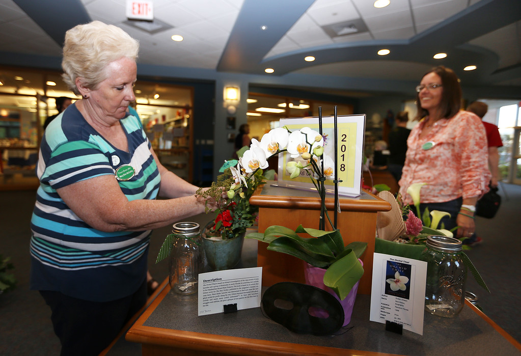 . Dracut Garden Club does Books in Bloom exhibit at Dracut Public Library. Mary Ellen McCarthy of Dracut, left, adjusts her arrangement. At right is Kristin McCauley of Dracut. (SUN/Julia Malakie)