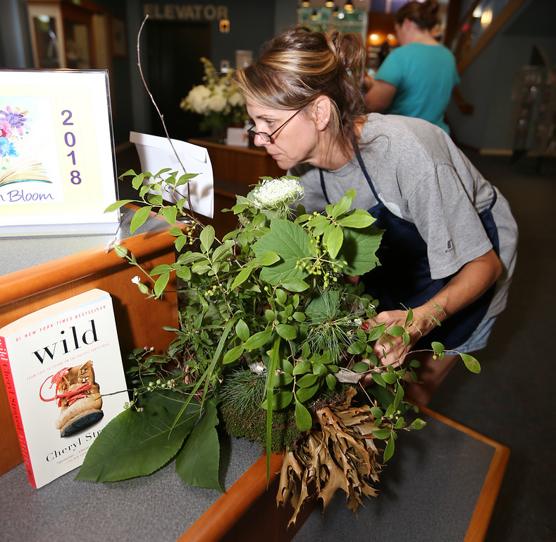 ". Dracut Garden Club does Books in Bloom exhibit at Dracut Public Library.  Lisa Bourgeois of Dracut, with her arrangement inspired by ""Wild\"" by Cheryl Strayed. (SUN/Julia Malakie)"