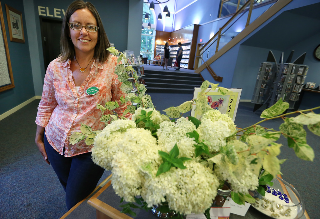""". Dracut Garden Club does Books in Bloom exhibit at Dracut Public Library.  Kristin McCauley of Dracut, with her arrangement inspired by the book \""""Lucia, Lucia\"""" by Adriana Trigiani. (SUN/Julia Malakie)"""