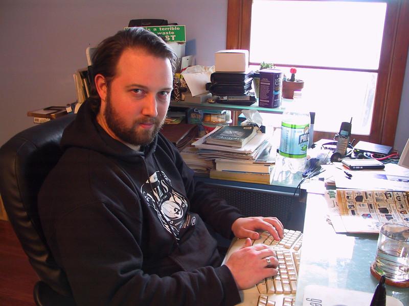 me, in hoodie, at desk