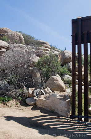 An abrupt end to the US-Mexican Internationall Border fence where the boundary line bumps against the rocky terrain of the Jacumba Mountains in Jacuma, California. The large boulder presents little challenge to anyone inclined to step around the fence.