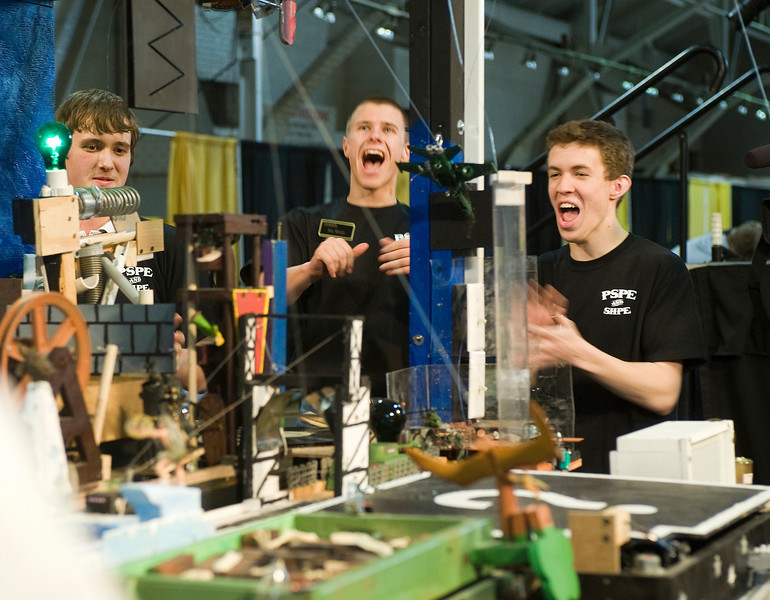 CO7/ Rube Goldberg Project <br /> <br /> Choice 7 of 10<br /> <br /> David Cannon (from left), Alex Weaver and Matt Miller react to a flawless run of their Purdue Society of Professional Engineers/Society of Professional Hispanic Engineers machine at the Purdue local Rube Goldberg competition Saturday (Feb. 26). The team won the competition and will compete in the national contest March 26 at Purdue.