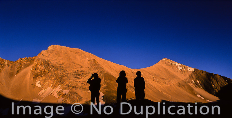 Hikers silhouetted against the White Cloud Peaks.