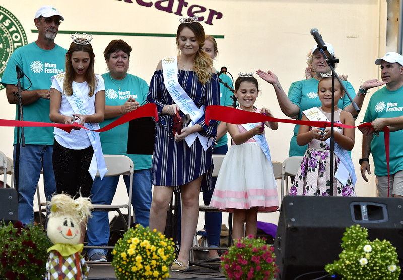 9/20/2018 Mike Orazzi   Staff Junior Miss Mum Carson Gagne, Miss Mum Kayla Paulette, Petite Miss Mum is Leah Aparo and Mini Miss Mum Gianna Cassin cut the ribbon to kick off this year's mum festival on Memorial Blvd. Thursday evening.