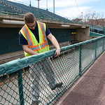 041017  Wesley Bunnell | Staff  Stadium preparation continues at the home of the New Britain Bees on Monday April 10.  Josh Prior uses plastic ties to secure the padding on the visitors side ...